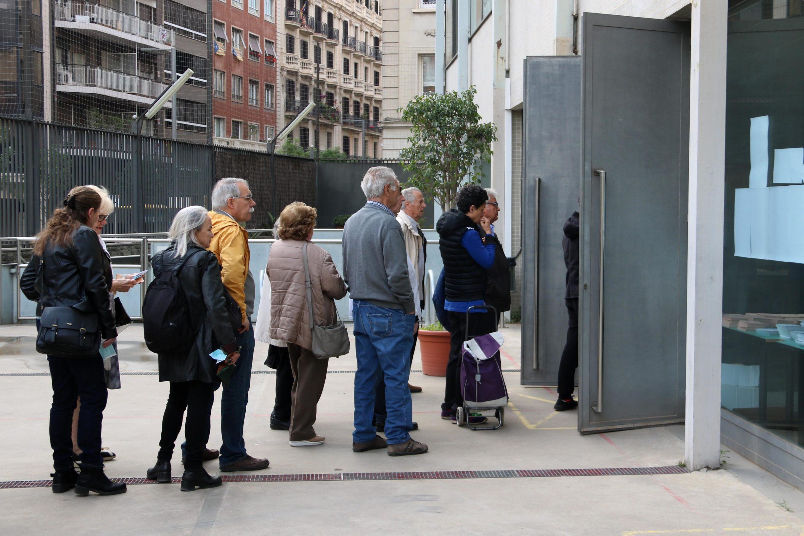 Cues d'electors esperant perquè obrin el d'Escola Oficial d'Adults de Sant Gervasi. / ACN (Aina Martí)
