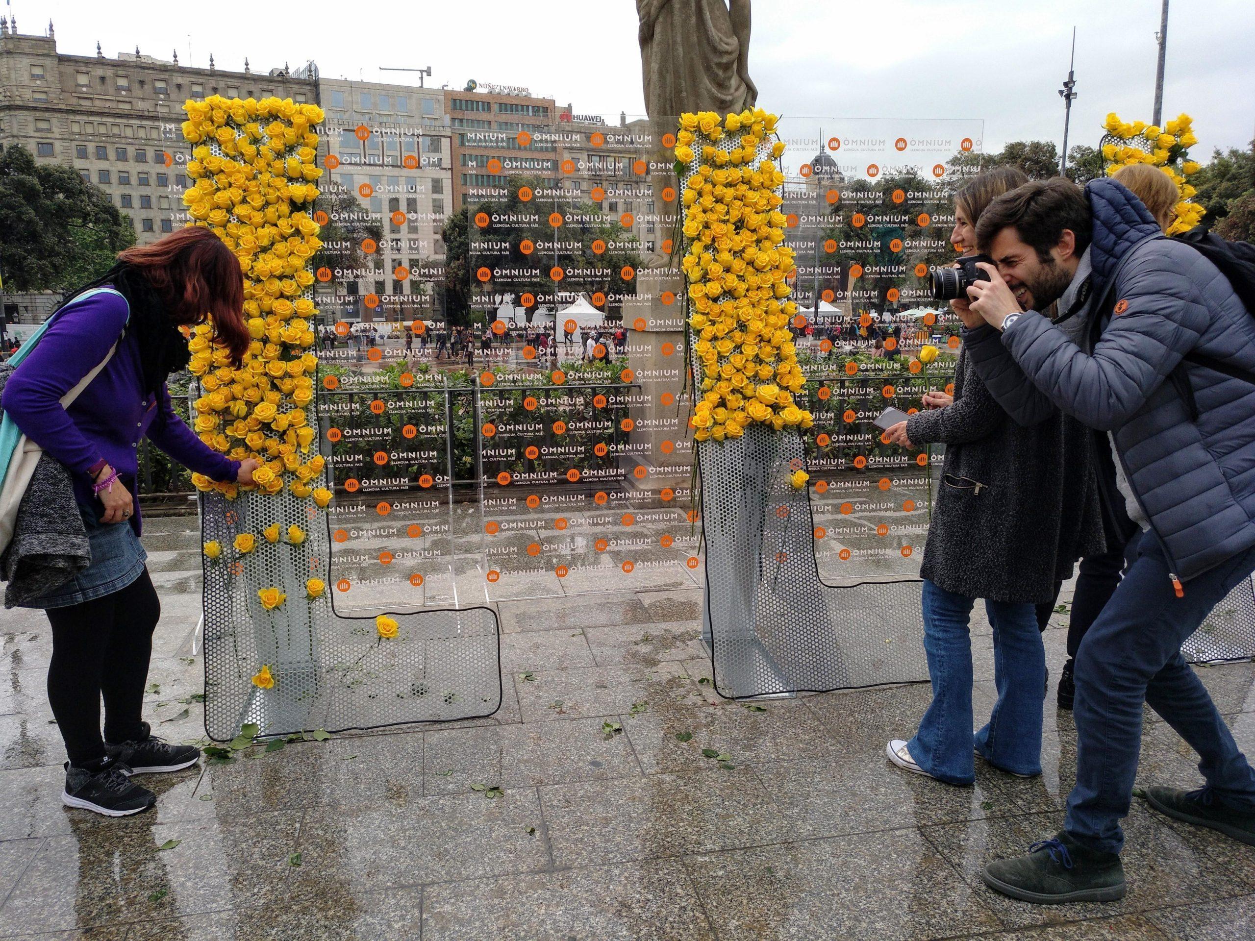 Una noia es fa fotografiar col·locant una rosa a la instal·lació d'Òmnium Cultural / MMP
