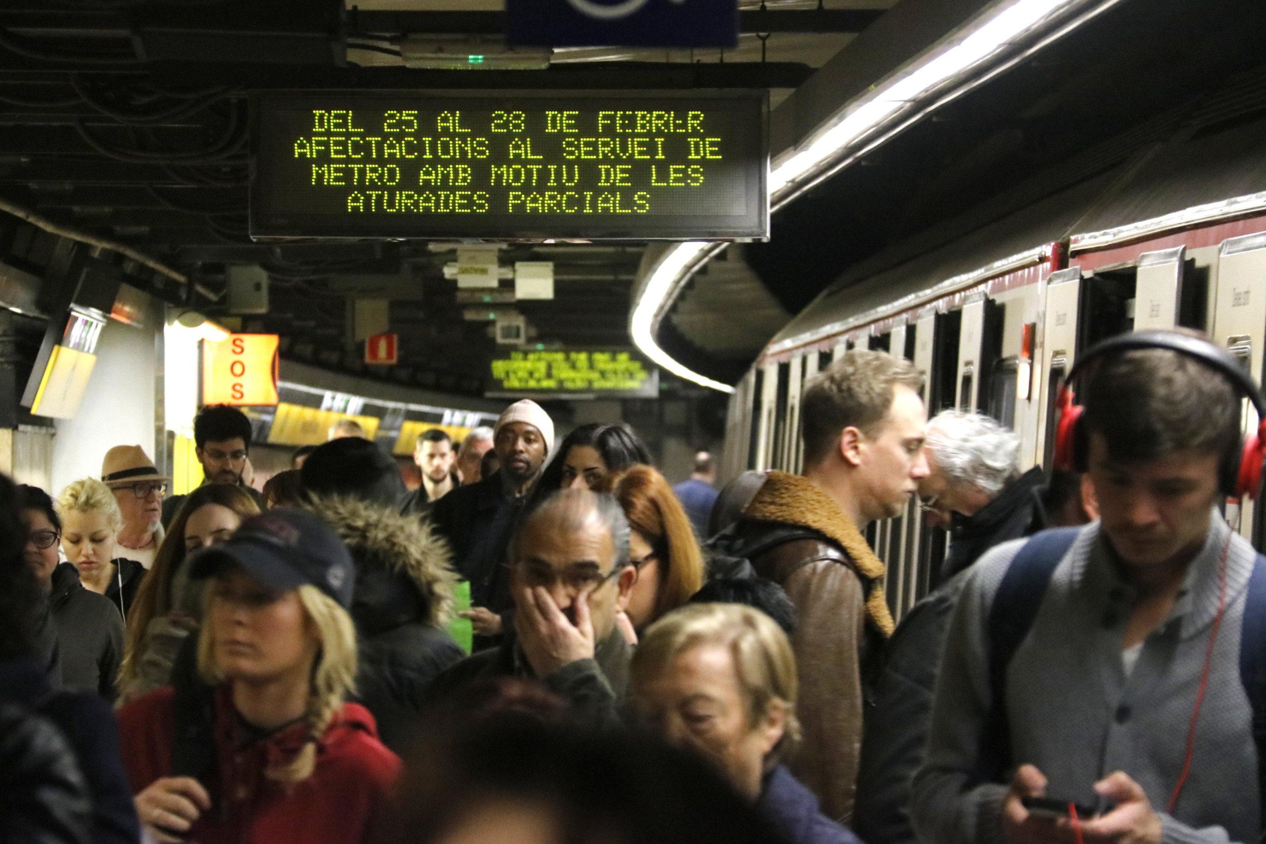 Un cartell anuncia de les afectacions de la vaga de metro davant l'aglomeració de passatgers, el 25 de febrer de 2019 / ACN
