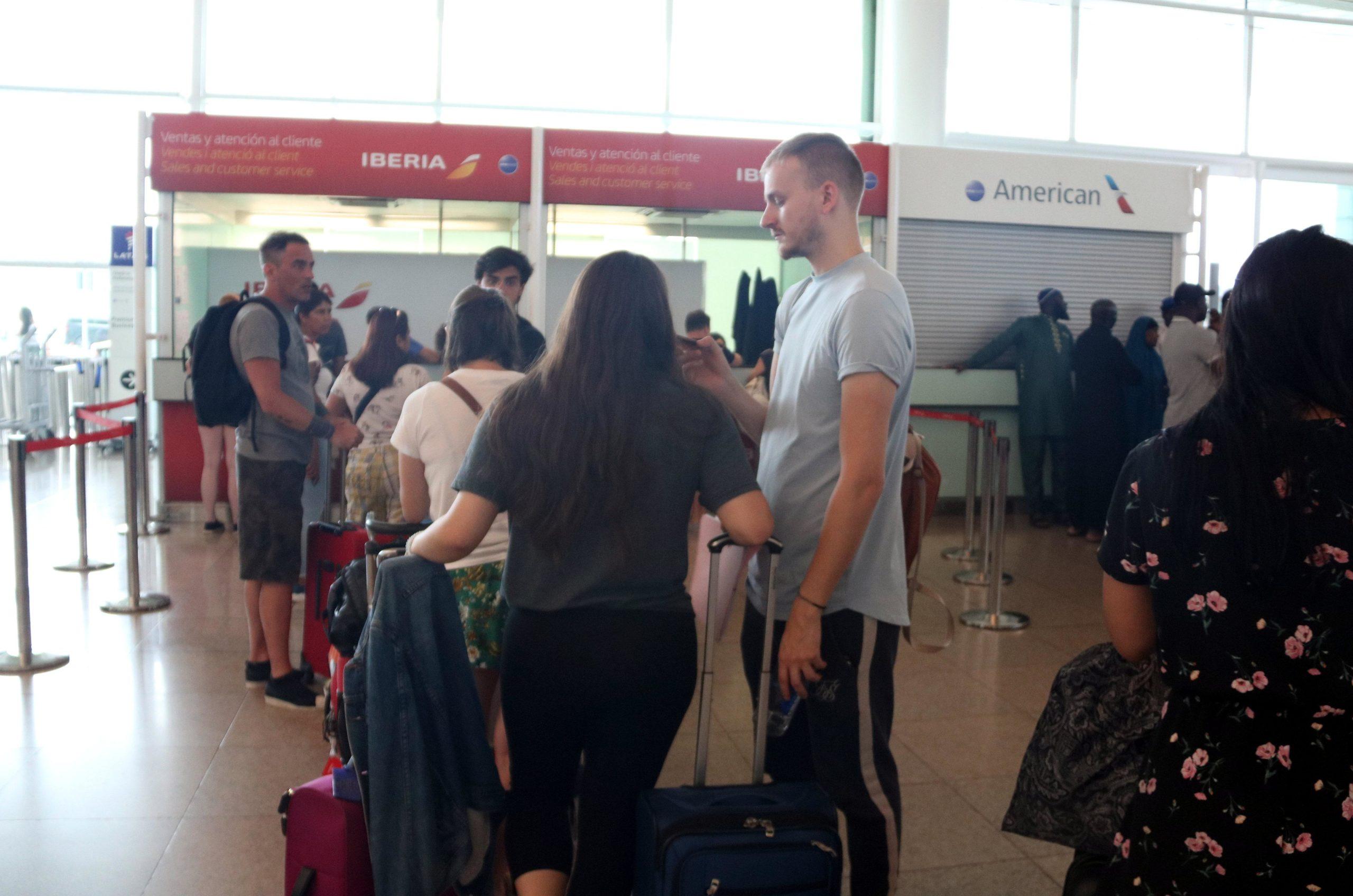 Diversos passatgers davant del taulell de reclamacions d'Ibèria a l'aeroport del Prat, el 27-7-2019 / ACN