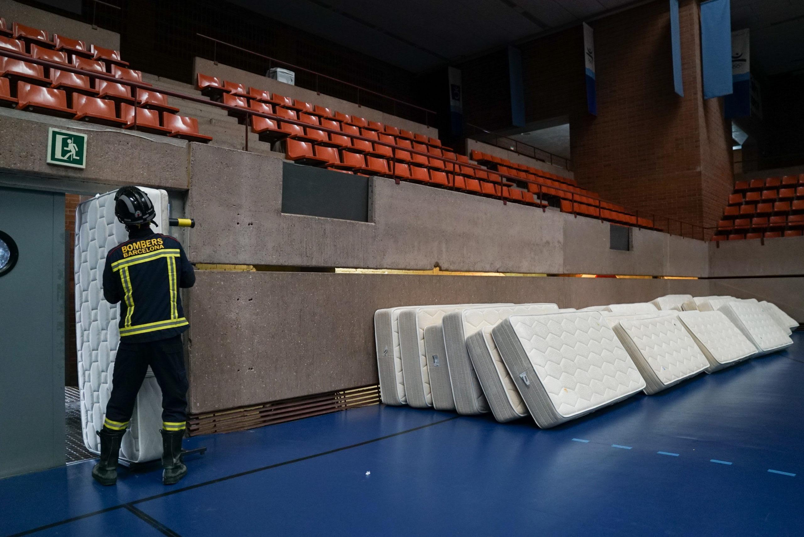 Un bomber col·loca llits a un dels poliesportius / Ajuntament de Barcelona