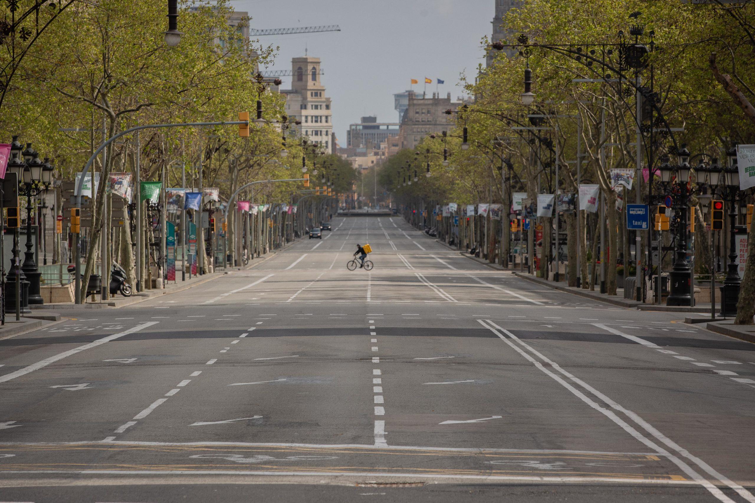 Un repartidor de Glovo en bicicleta, rei del passeig de Gràcia buit, durant l'estat d'alarma a Barcelona pel coronavirus / David Zorrakino - Europa Press