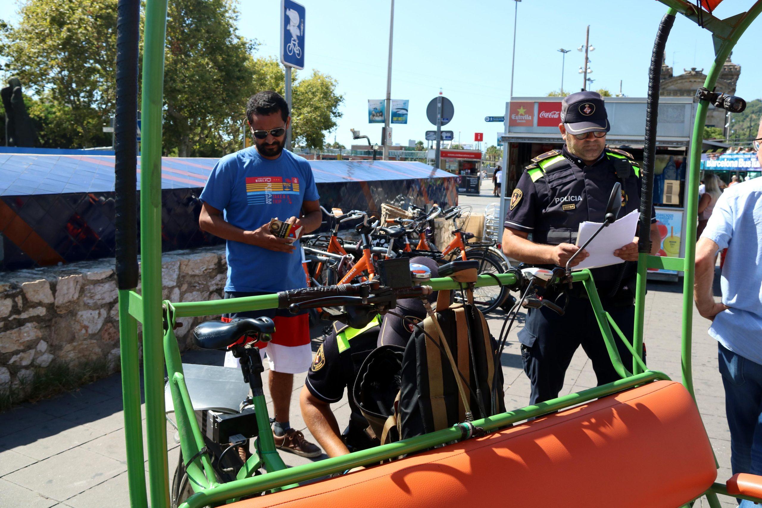 Un agent de la Guàrdia Urbana revisant els papers d'un bicitaxi / ACN - Elisenda Rosanas
