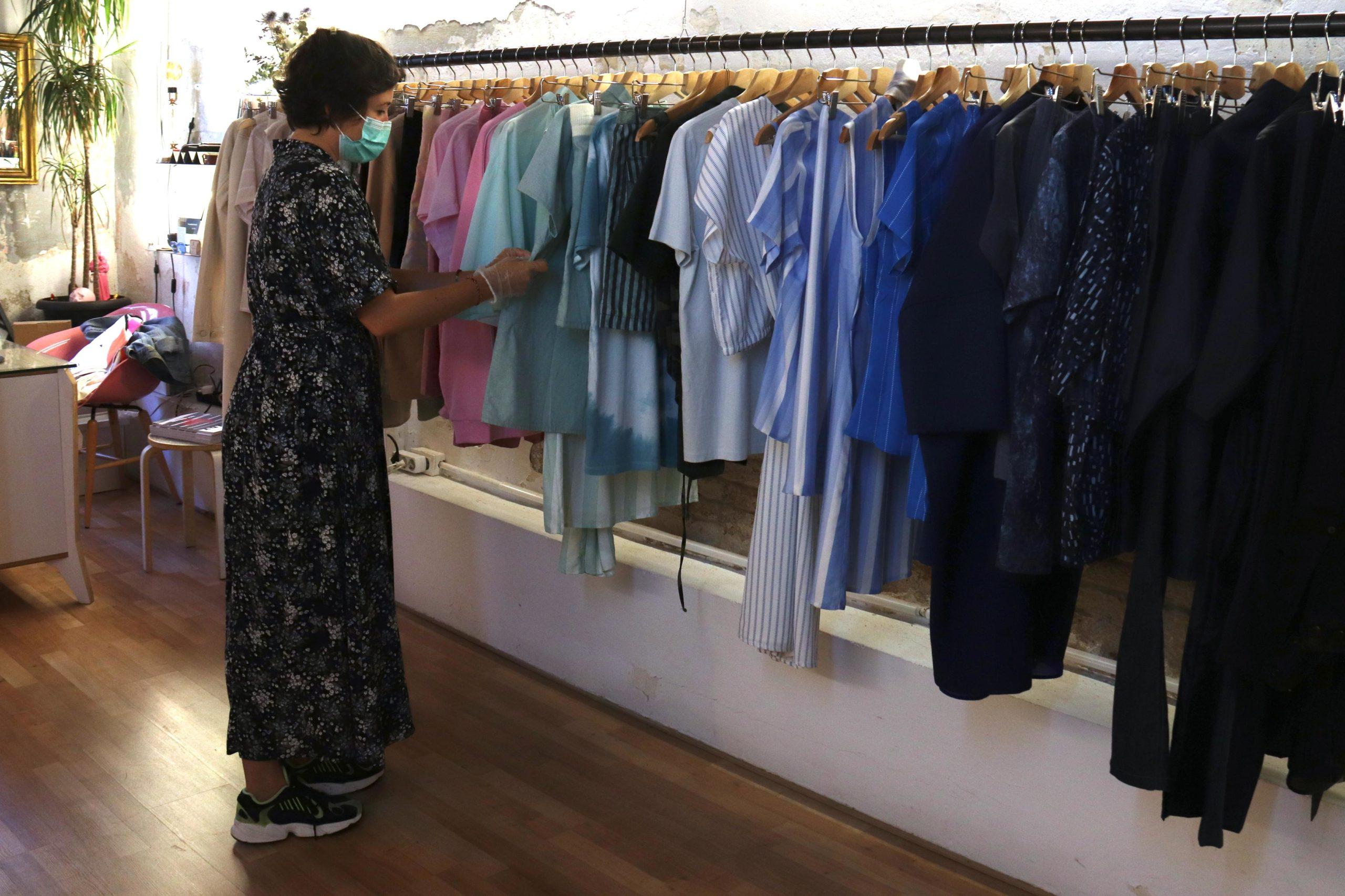 La propietària d'una botiga de roba de Gràcia col·locant bé les peces, el primer dia de fase zero i mig / ACN