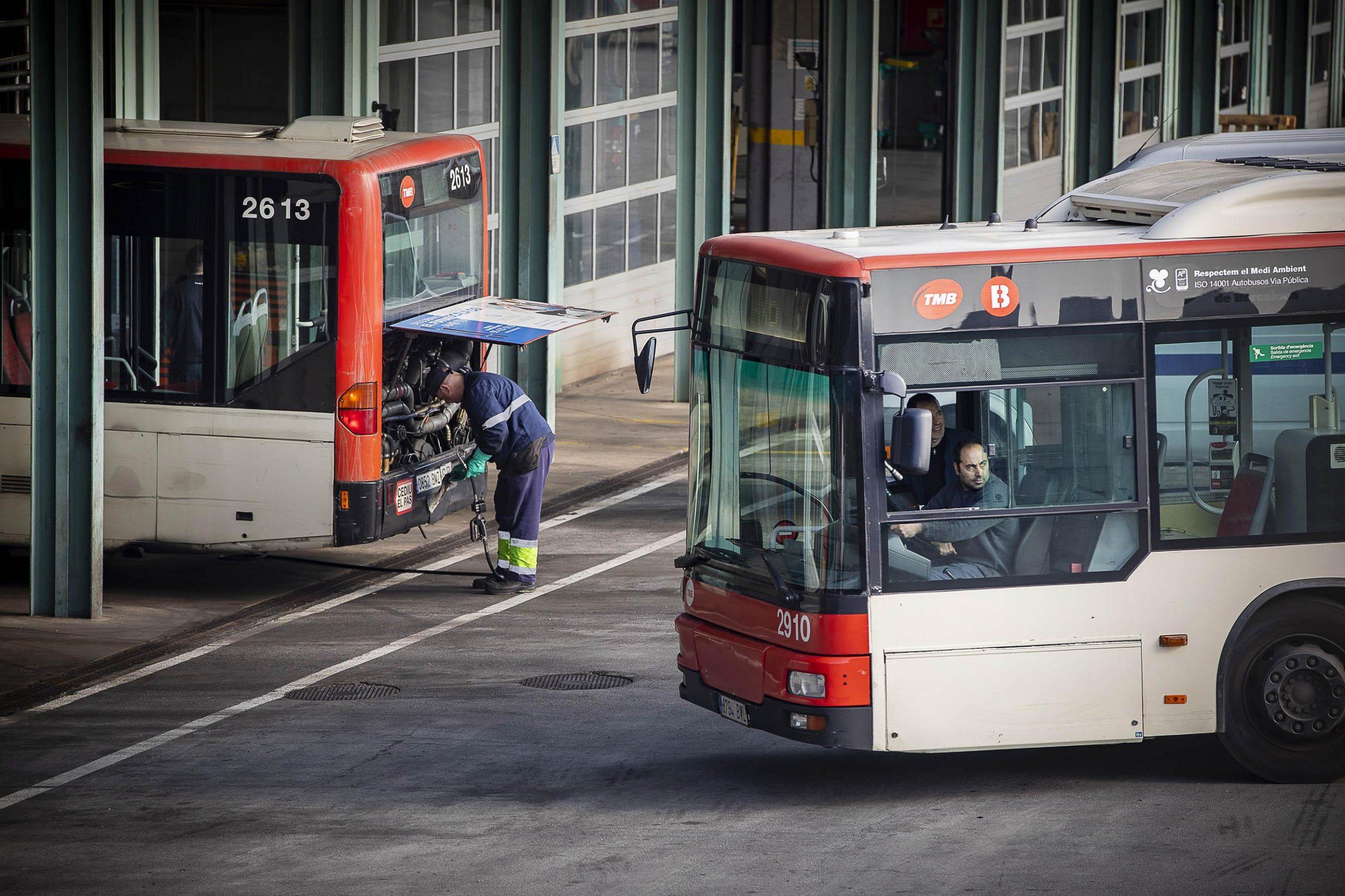 Un conductor de bus entra a les cotxeres d'Horta mentre un altre treballador revisa un vehicle, en imatge d'arxiu / Jordi Play
