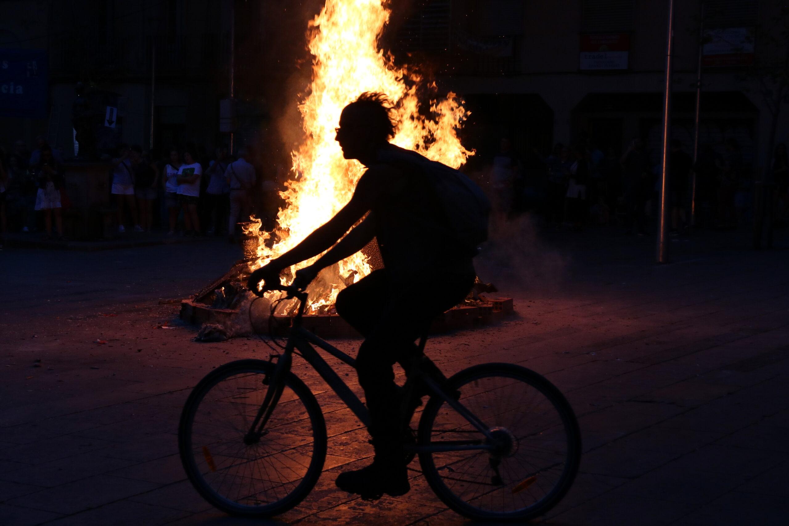 Contrallum d'una bicicleta passant per davant d'una foguera de Sant Joan a la plaça de la Virreina de Barcelona / ACN