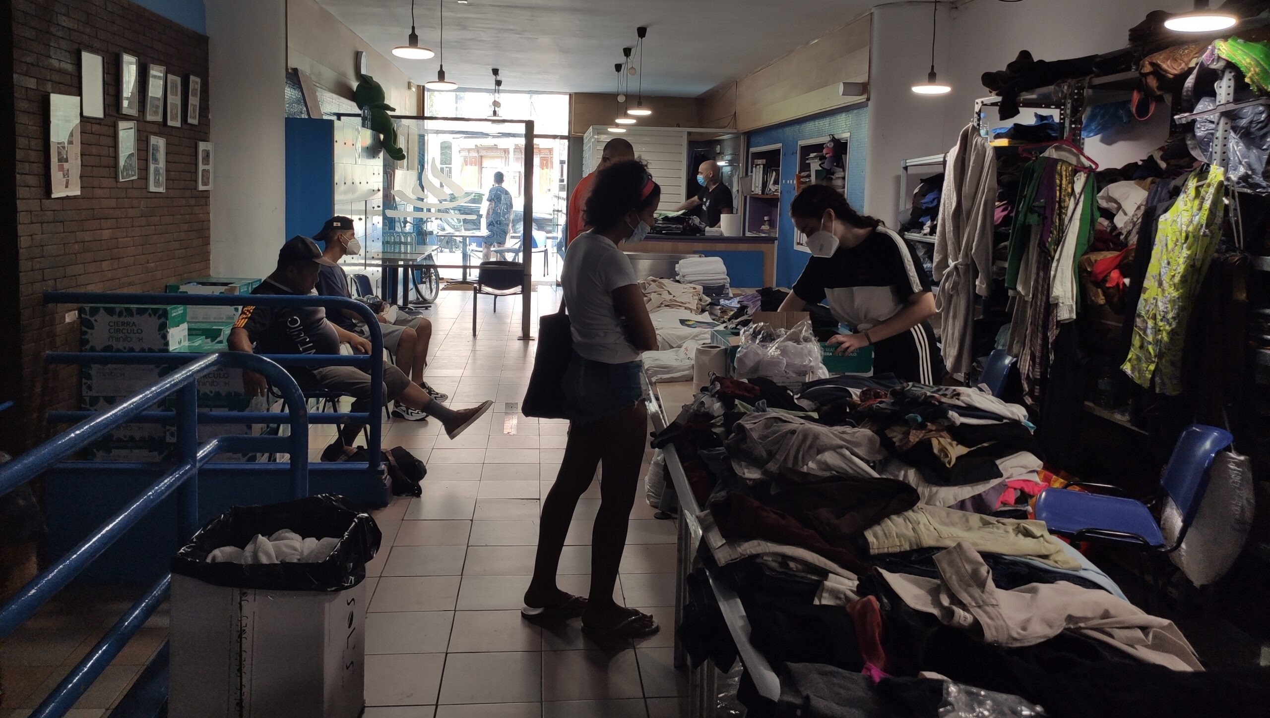 Els treballadors del Sant Pau oferint roba als usuaris / Gimnàs Social Sant Pau