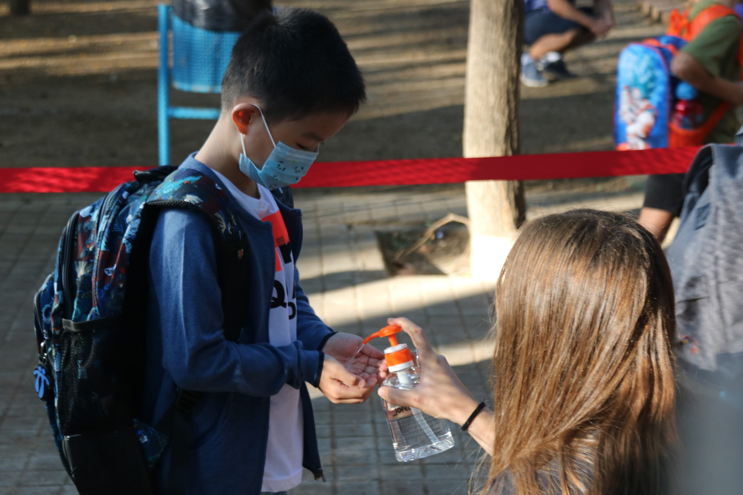 Un alumne de l'Escola Catalònia de Barcelona posant-se gel desinfectant a l'entrada del centre en el primer dia de classes / ACN