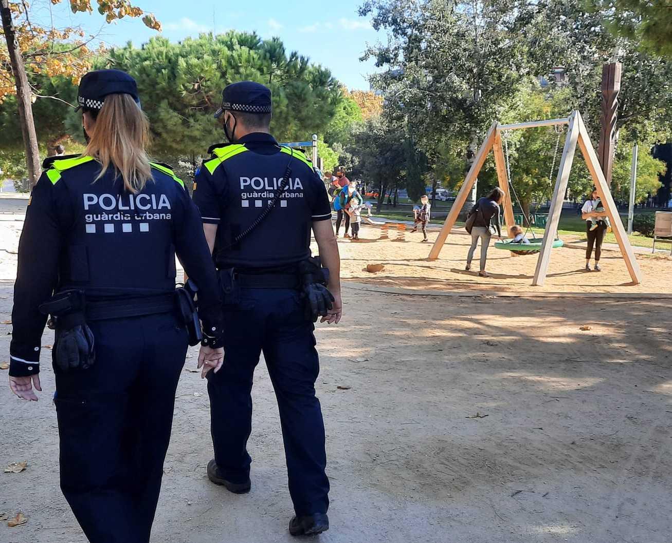 Dos agents de la Guàrdia Urbana patrullant en un parc infantil / GUB