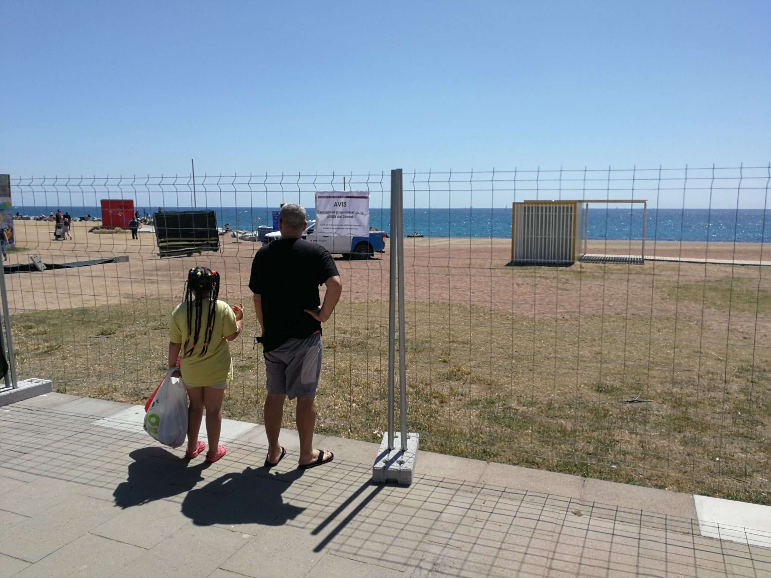 Dues persones llegeixen el cartell que informat del tancament de la platja de Sant Adrià del Besòs / TOT Barcelona