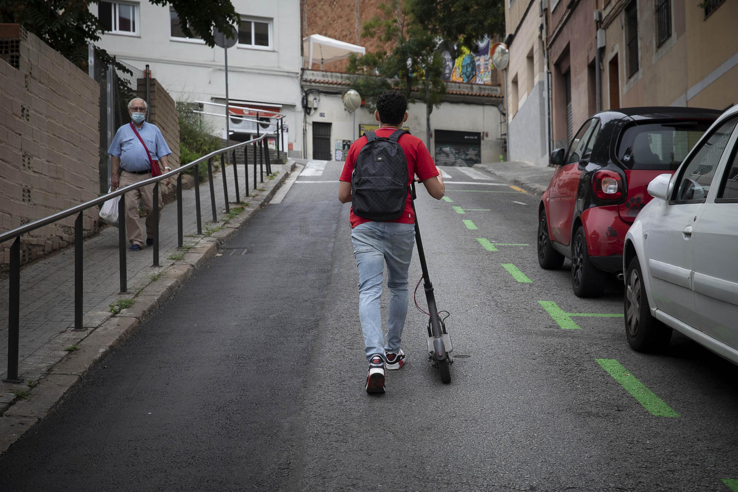 Un usuari de patinet elèctric, acabant la pujada a peu per la falta de potència necessària / Jordi Play
