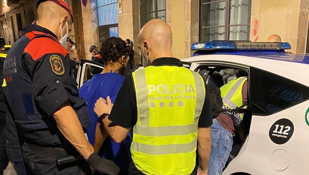 Agents dels Mossos i la Urbana entren un detingut a un cotxe patrulla / GUB