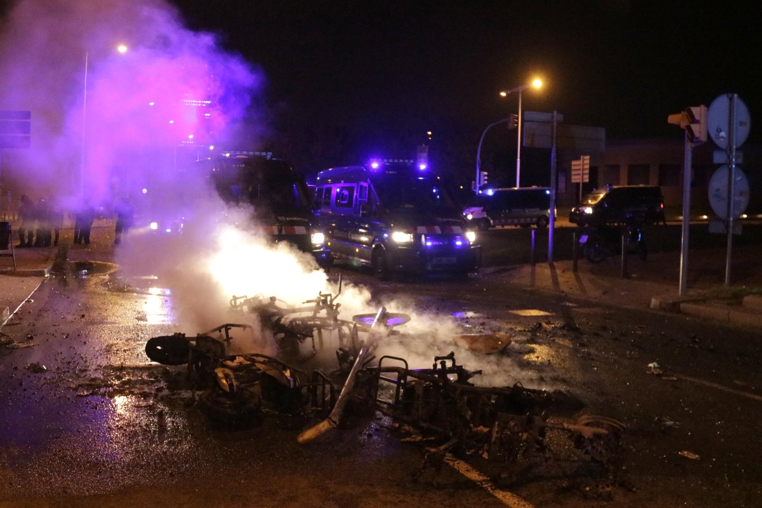 Motos cremades davant els furgons dels Mossos d'Esquadra al fons, al botellot del Bogatell / ACN