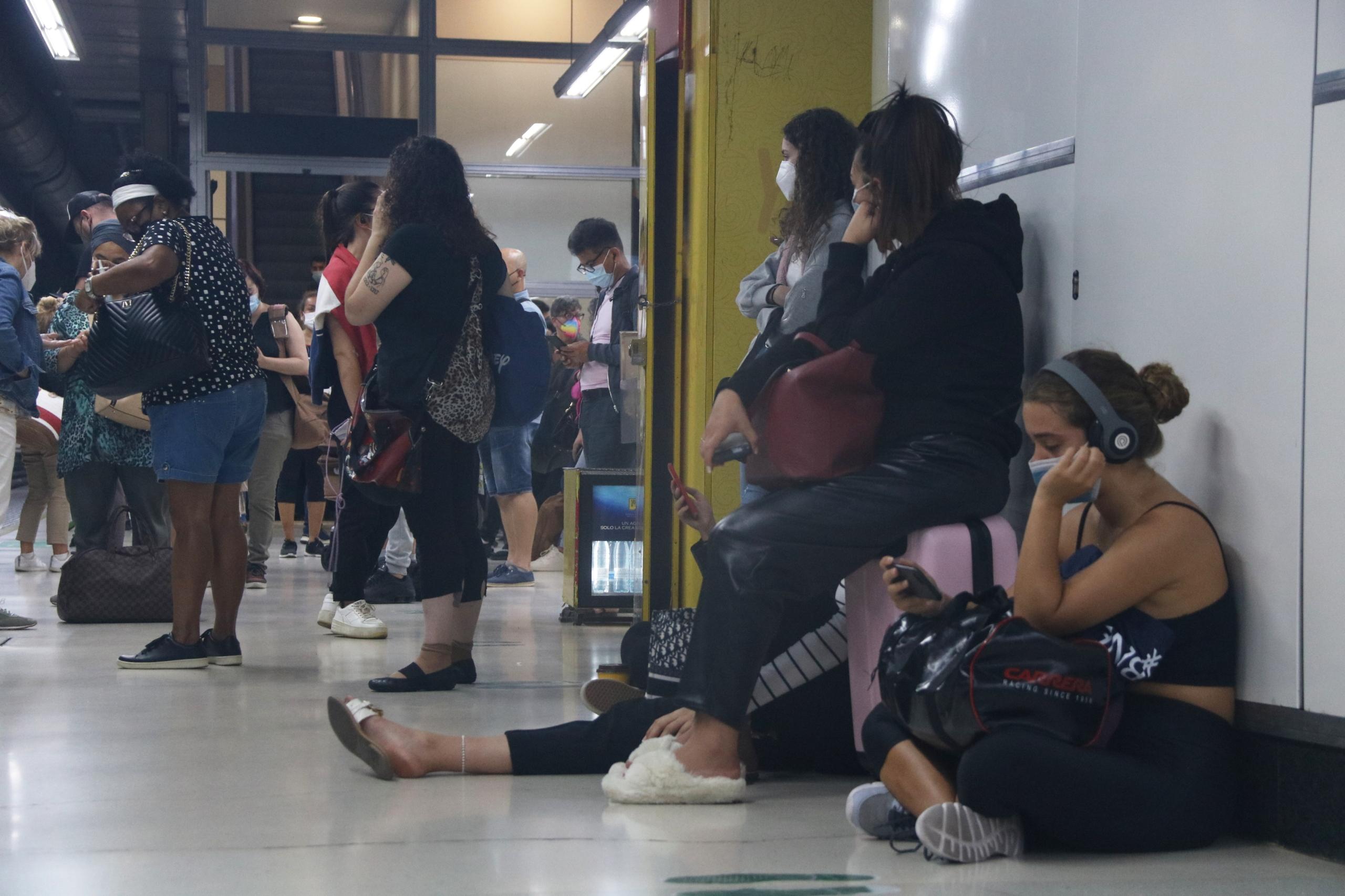 Diversos passatgers de Renfe esperant el seu tren a una de les andanes de l'estació de Sants / ACN